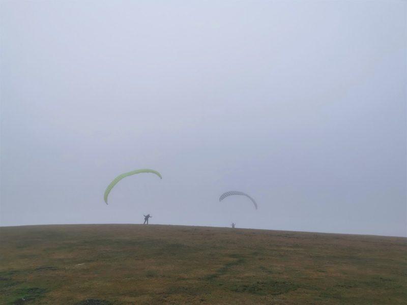 Gleitschirmflieger auf der Wasserkuppe im Nebel - auf der Extratour Guckaisee in der Rhön